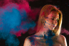 Attractive blond girl in colors paints Stock Images