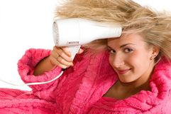 Attractive blond girl with a drier. Picture of an attractive blond girl with a drier Royalty Free Stock Image