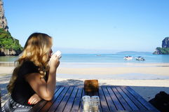 Attractive blond girl drinking coffee by the beach Royalty Free Stock Photography