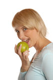 Attractive blond girl eating an apple Stock Photography
