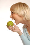 Attractive blond girl eating an apple Royalty Free Stock Photo