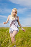 Attractive blond girl on field Stock Images