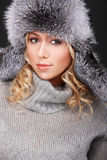 Attractive blond girl in fur hat Stock Photos