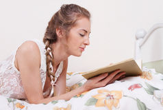 Attractive blond girl with hairdress reading Stock Photos