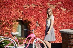 Attractive blond girl at pink lady bicycle on sunny day on wall overgrown with red ivy background. Young pretty smiling blond woman in casual clothing and stock photography