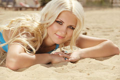 Attractive blond girl sunbathing on beach Royalty Free Stock Images