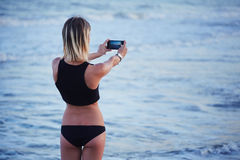 Attractive blond girl taking picture of beautiful view of the sea at sunset. Athletic girl running standing on the beach and taking picture of beautiful view of stock images