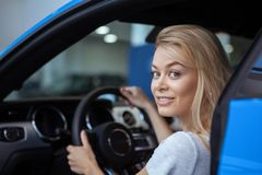 Beautiful young woman buying new car at the dealership royalty free stock image
