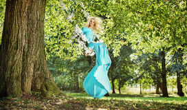 Attractive blond lady on a flower seesaw in a park Royalty Free Stock Images
