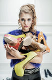 Attractive blond lady holding a bunch of shoes stock image