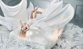 Attractive blond lady lying on pure white sheet Royalty Free Stock Images