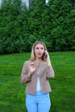 Attractive blond lady talking on phone and holds it in hand, smi Stock Photo