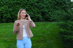 Attractive blond lady talking on phone and holds it in hand, smi Royalty Free Stock Photo