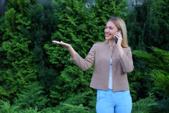 Attractive blond lady talking on phone and holds it in hand, smi Royalty Free Stock Photos