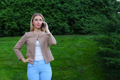 Attractive blond lady talking on phone and holds it in hand, smi Royalty Free Stock Photography