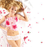 Attractive blond lying on a white blanket. Covered with pink petals stock images