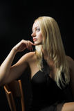 Attractive blond model on black background. Black dress - very high resolution - sitting on the chair Stock Photos