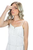 Attractive blond model having headache touching her forehead Stock Photos