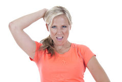 Attractive blond model in orange shirt looking at camera one arm Royalty Free Stock Photos