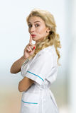 Attractive blond nurse gesturing silence. Young woman in lab coat making silence gesture, shhh. Keep the silence gesture Royalty Free Stock Image