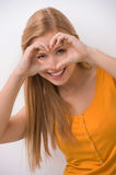 Attractive blond showing heart and smiling. Royalty Free Stock Photography