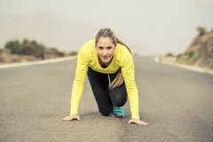 Attractive blond sport woman ready to start running practice training race starting on asphalt road mountain landscape. Young attractive blond sport woman ready Royalty Free Stock Image