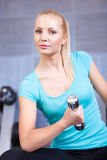 Attractive blond sporty girl doing biceps training Stock Images