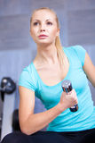 Attractive blond sporty girl doing biceps training with a dumbbell Royalty Free Stock Photography