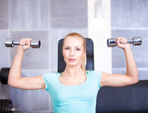 Attractive blond sporty girl doing shoulders training Stock Image
