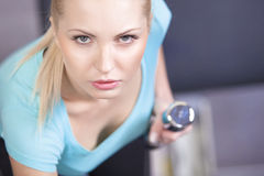 Attractive blond sporty girl doing triceps training with a dumbbell Stock Photography