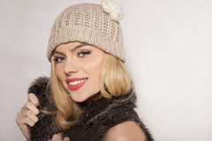 Attractive blond in a winter jacket and beanie. Attractive young blond in a stylish furry winter jacket and knitted beanie looking at the camera with a lovely Royalty Free Stock Photos