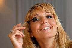 Attractive blond woman applying eye mascara Stock Photo