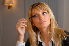 Attractive blond woman applying eye mascara Royalty Free Stock Images