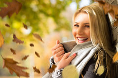 Attractive blond woman in the autumn sun. With falling leaves Stock Photo