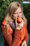 Attractive blond woman biting into an apple Royalty Free Stock Image