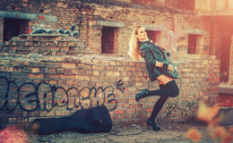 Attractive blond woman in black body suit,dark stockings, leather jacket standing on the roof of the old building and holds a guit Stock Photo