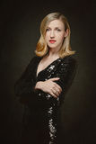 Attractive blond woman in a black cocktail dress Royalty Free Stock Image