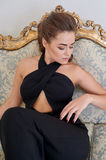 Attractive blond woman in black dress sitting on the couch Royalty Free Stock Images