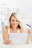 Attractive blond woman with a credit card and a tablet computer Stock Photos