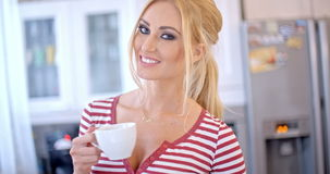 Attractive blond woman drinking fresh coffee stock footage