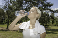 Attractive blond woman drinking water. Portrait of attractive blond woman drinking water royalty free stock image