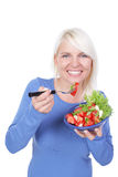 Attractive blond woman eats salat with tomato and mozarella Royalty Free Stock Photo
