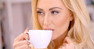 Attractive blond woman enjoying a hot beverage Royalty Free Stock Image