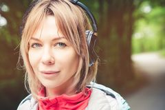 Attractive blond woman in the forest. Close-up portrait of a sporty smiling girl listening to music royalty free stock images