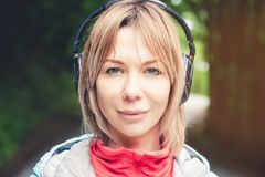 Attractive blond woman in the forest. Close-up portrait of a sporty smiling girl listening to music royalty free stock photo