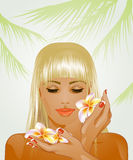 Attractive blond woman with frangipani flowers Royalty Free Stock Photos