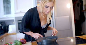 Attractive blond woman frying fresh vegetables stock footage