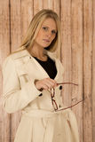 Attractive blond woman holding glasses in white coat with woode Stock Images