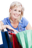 An attractive blond woman holding a paper shopping bag. Royalty Free Stock Photography