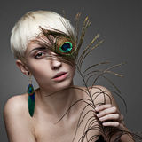 Attractive blond woman holding peacock feather Stock Images